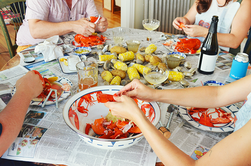 group of friends eating lobster boil with golden rabbit enamelware